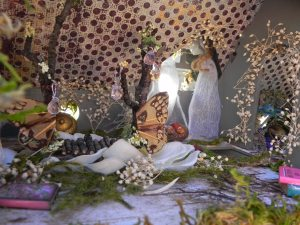 The bedroom's fairy bed has butterfly wings, ornaments, and rests upon a nest of flower petals...